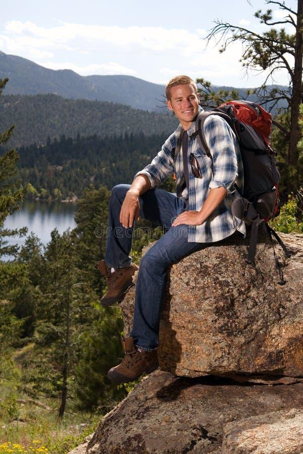 Homem que senta-se em uma rocha imagem de stock royalty free