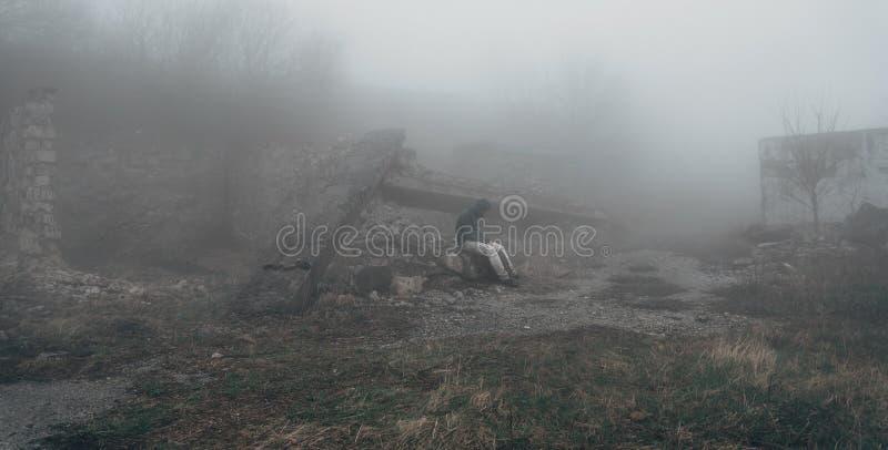 Homem que senta-se entre as ruínas foto de stock