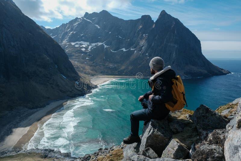 Homem que senta-se na borda do penhasco apenas que aprecia férias exteriores backpacking da aventura do curso do estilo de vida d foto de stock royalty free
