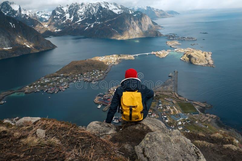 Homem que senta-se na borda do penhasco apenas que aprecia férias exteriores backpacking da aventura do curso do estilo de vida d imagens de stock