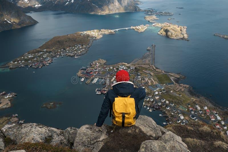Homem que senta-se na borda do penhasco apenas que aprecia férias exteriores backpacking da aventura do curso do estilo de vida d imagem de stock royalty free