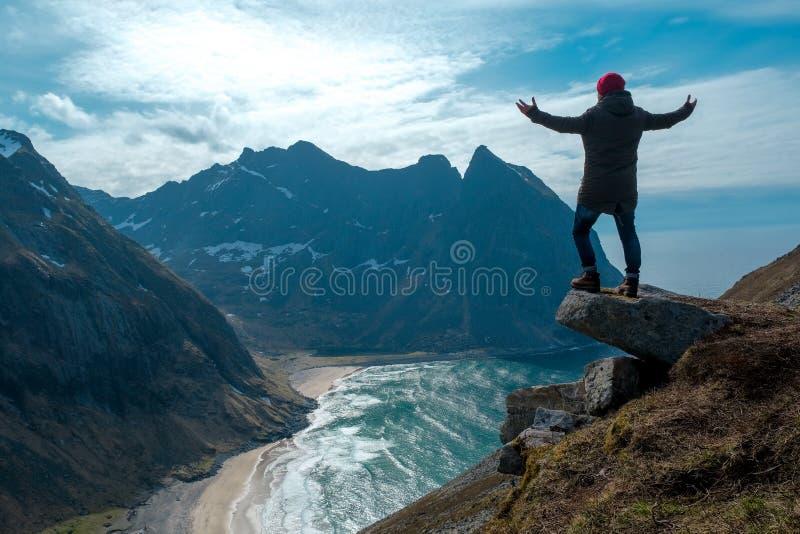 Homem que senta-se na borda do penhasco apenas que aprecia férias exteriores backpacking da aventura do curso do estilo de vida d fotografia de stock royalty free