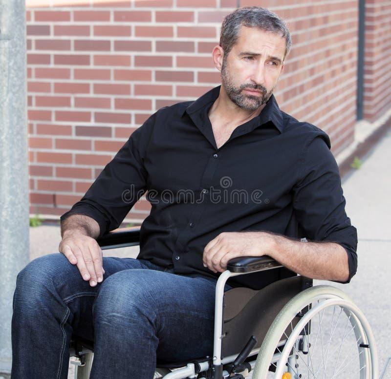 Homem que senta-se na cadeira de rodas que olha comprimida imagem de stock royalty free