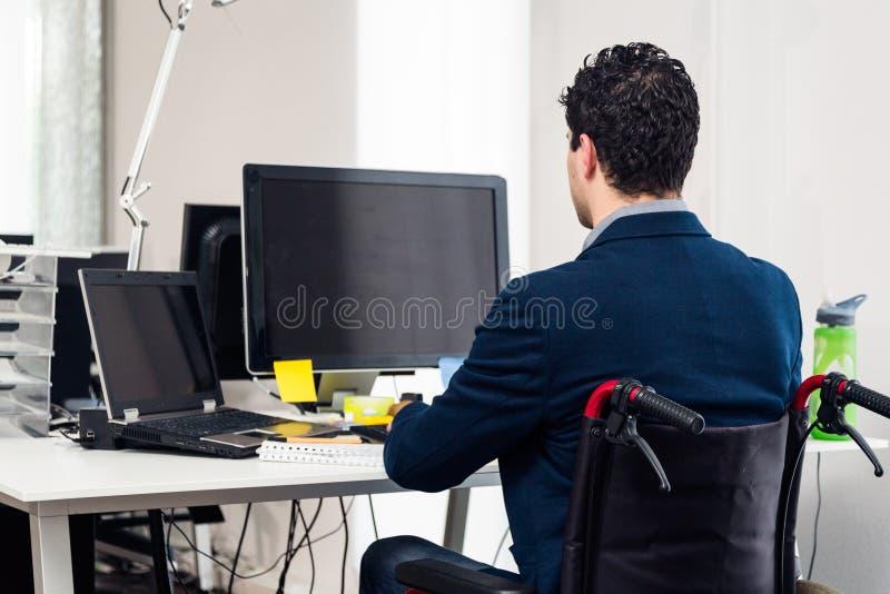 Homem que senta-se na cadeira de rodas que trabalha no escritório moderno fotografia de stock royalty free