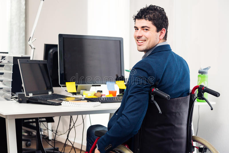 Homem que senta-se na cadeira de rodas que trabalha no escritório moderno imagens de stock