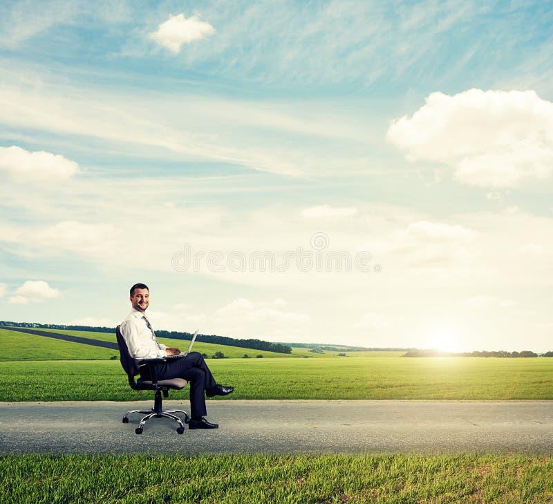 Homem que senta-se na estrada e no trabalho imagens de stock