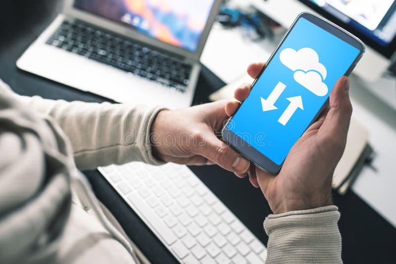 Homem que senta-se na mesa de escritório usando o serviço da nuvem no smartphone para transferência e a sincronização de dados fotos de stock