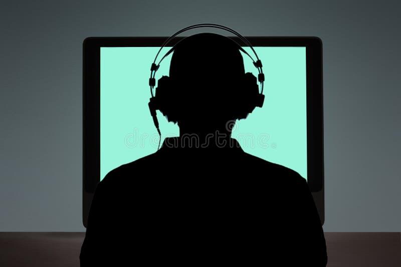 Homem que senta-se na mesa na frente de um computador com espaço da cópia para seu texto imagem de stock