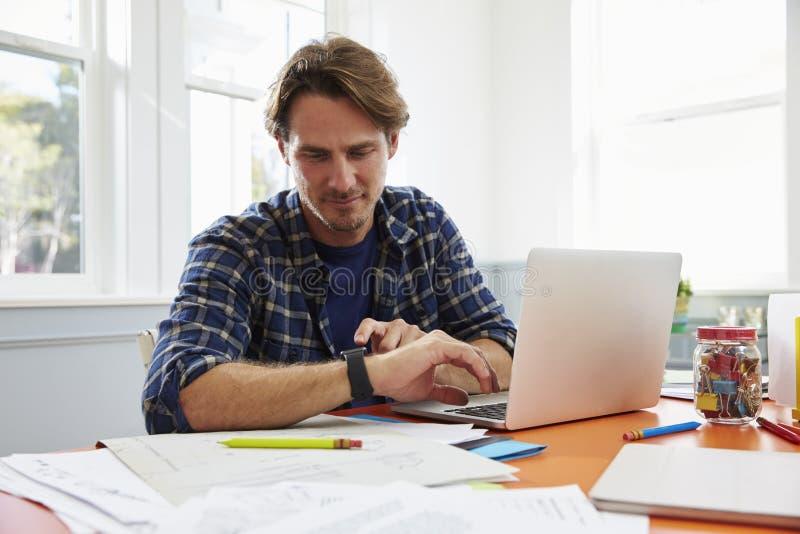 Homem que senta-se na mesa no escritório domiciliário que olha o relógio esperto fotos de stock royalty free
