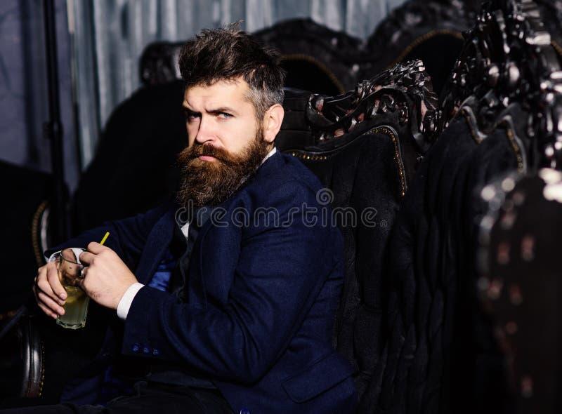 Homem que senta-se na poltrona de couro no interior luxuoso imagens de stock