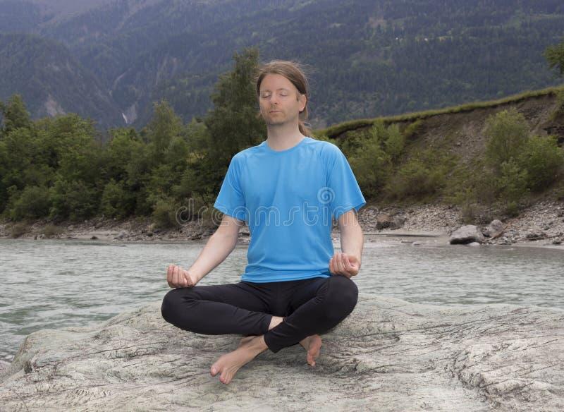 Homem que senta-se na pose de Lotus e que medita por um rio fotos de stock royalty free