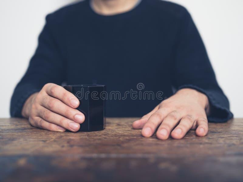 Homem que senta-se na tabela com copo imagens de stock