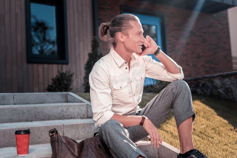 Homem que senta-se nas escadas fora de comer o café e do falar pelo telefone fotos de stock