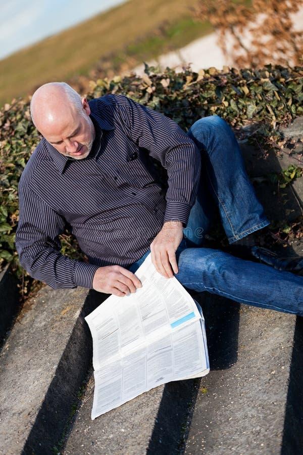 Homem que senta-se nas etapas que leem um jornal fotos de stock royalty free