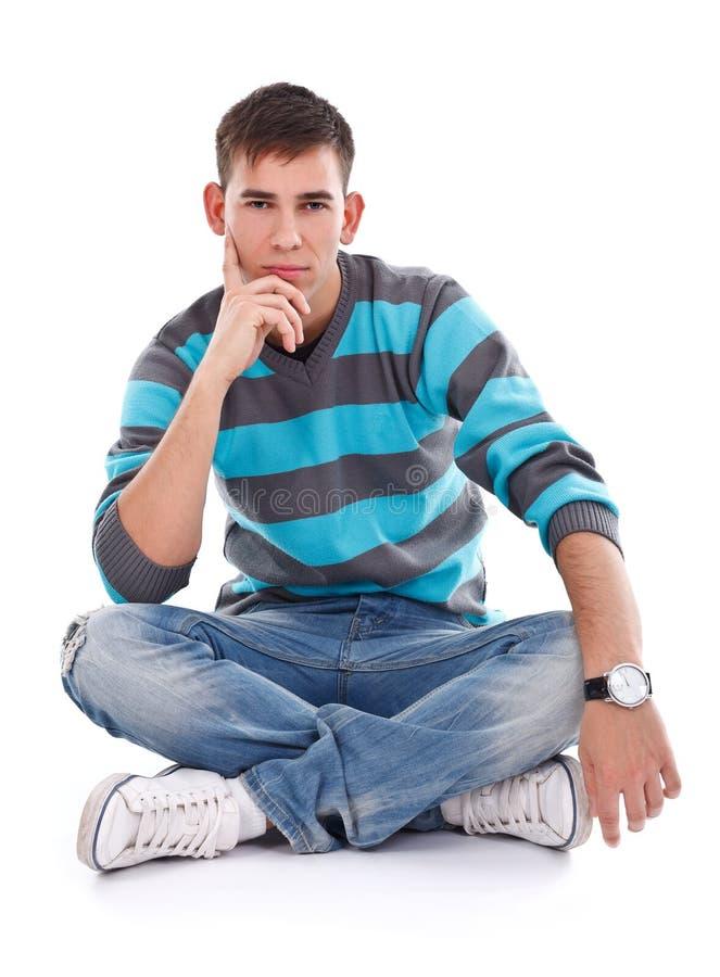 Homem que senta-se no assoalho fotografia de stock royalty free