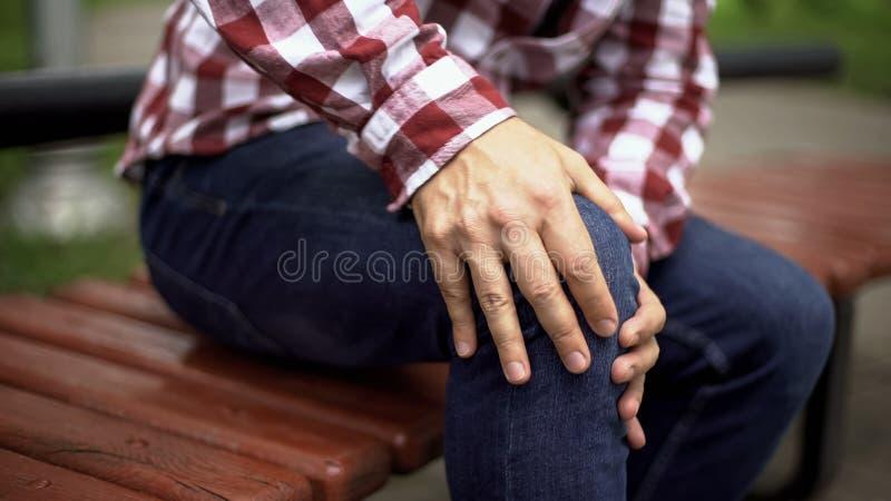 Homem que senta-se no banco que sente a dor afiada do joelho, osteodistrofia, ferimento, cuidados médicos fotos de stock