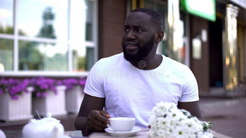 Homem que senta-se no café com o ramalhete das flores na tabela, amiga de espera da virada imagens de stock royalty free