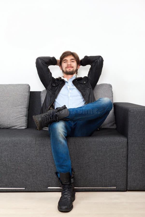 Homem que senta-se no moderno do indivíduo da sala de visitas do sofá imagens de stock