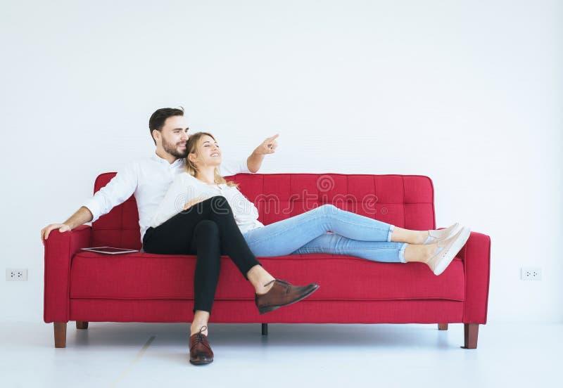 Homem que senta-se no sofá vermelho com a mulher e a mão que indicam a janela na sala de visitas na casa, feliz e sorrindo, em da foto de stock
