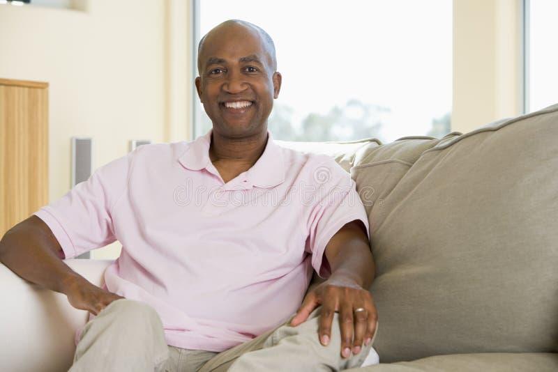Homem que senta-se no sorriso da sala de visitas imagem de stock
