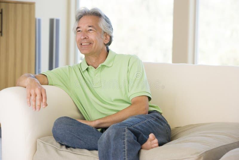 Homem que senta-se no sorriso da sala de visitas imagens de stock