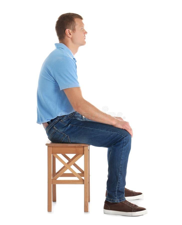 Homem que senta-se no tamborete contra o fundo branco imagem de stock