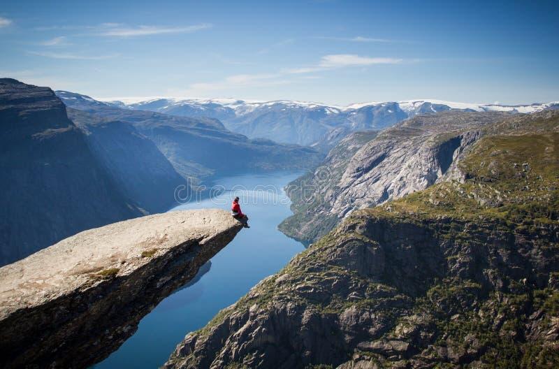 Homem que senta-se no trolltunga em Noruega foto de stock
