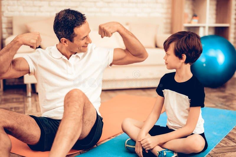 Homem que senta-se nos músculos do menino da exibição do assoalho em casa imagem de stock