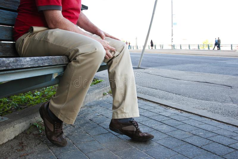 Homem que senta-se ou que espera pacientemente no banco imagens de stock