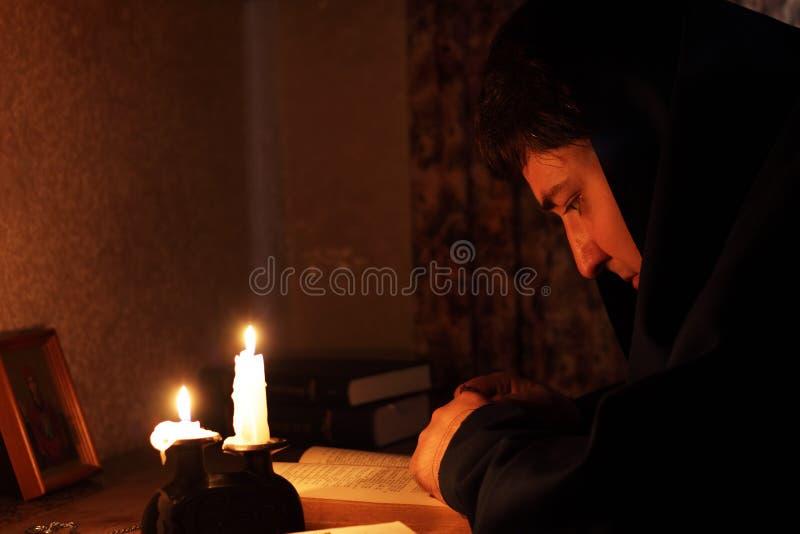 Homem que senta-se pela luz de vela foto de stock