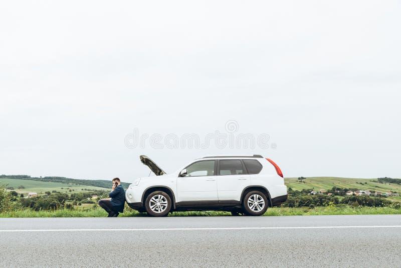 Homem que senta-se perto de carro quebrado com o telefone, procurando a ajuda foto de stock royalty free