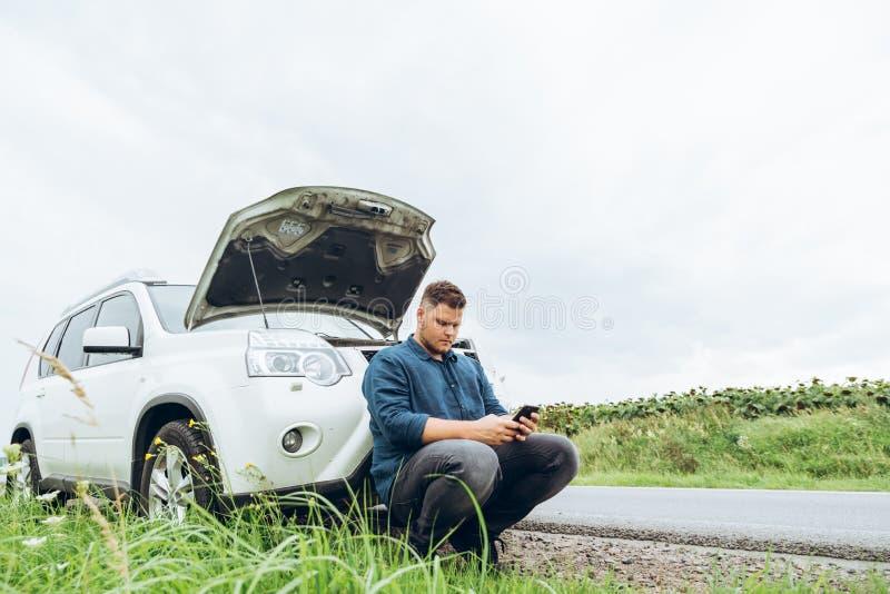 Homem que senta-se perto de carro quebrado com o telefone, procurando a ajuda imagens de stock
