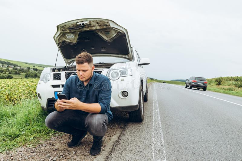 Homem que senta-se perto de carro quebrado com o telefone, procurando a ajuda imagem de stock royalty free