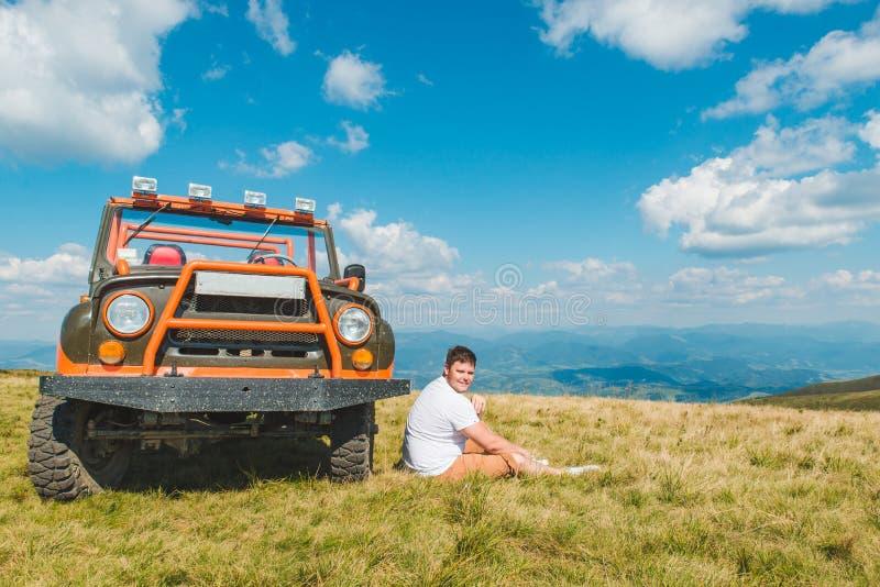 Homem que senta-se perto do carro do suv na parte superior da montanha com vista bonita imagem de stock royalty free