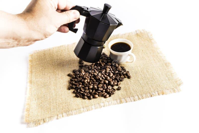 Homem que serve uma xícara de café com um fabricante de café italiano ao lado de uma pilha de feijões de café em uma toalha de me foto de stock