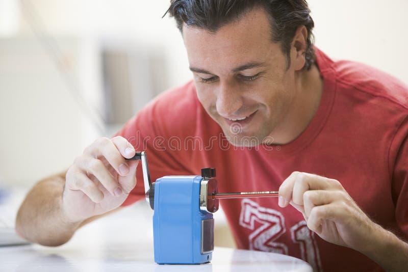 Homem que sharpening o lápis imagens de stock