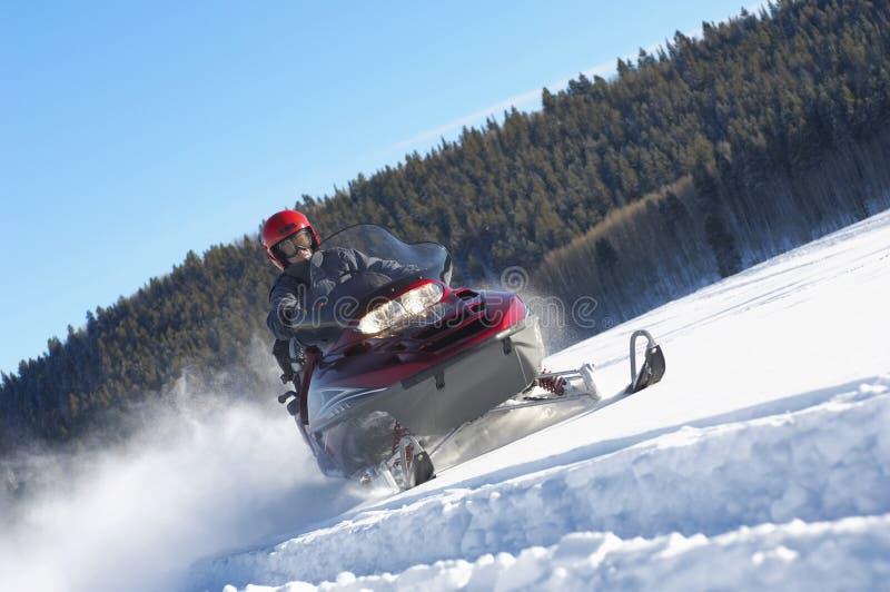 Homem que Snowmobiling através da neve fotografia de stock royalty free