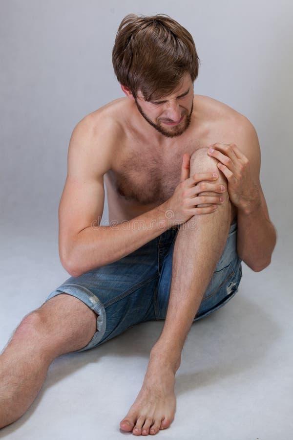 Homem que sofre da dor do joelho fotografia de stock royalty free