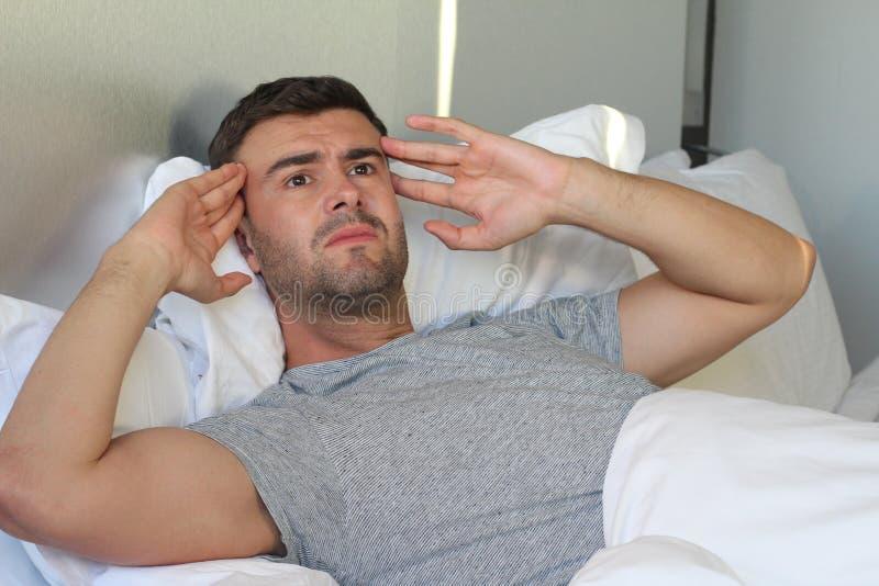 Homem que sofre da dor na cama imagem de stock royalty free