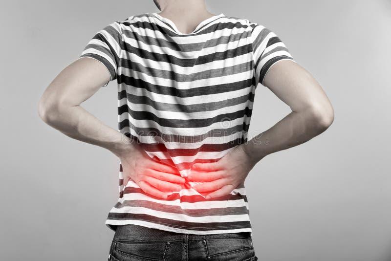 Homem que sofre da dor nas costas no fundo cinzento imagem de stock