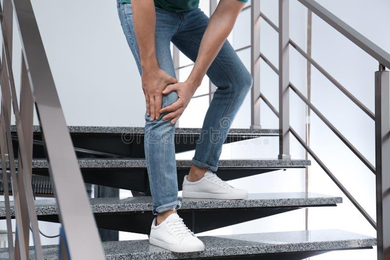 Homem que sofre de dor no joelho enquanto desce para dentro Problemas de saúde imagens de stock