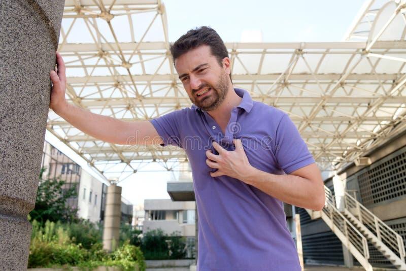 Homem que sofre para um cardíaco de ataque mau foto de stock royalty free