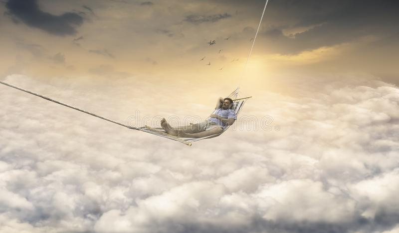 Homem que sonha na rede de balanço acima do céu imagens de stock royalty free