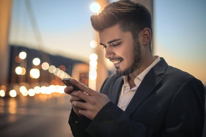 Homem que sorri em seu telefone foto de stock royalty free