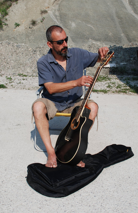 Homem que substitui cordas da guitarra fotografia de stock royalty free