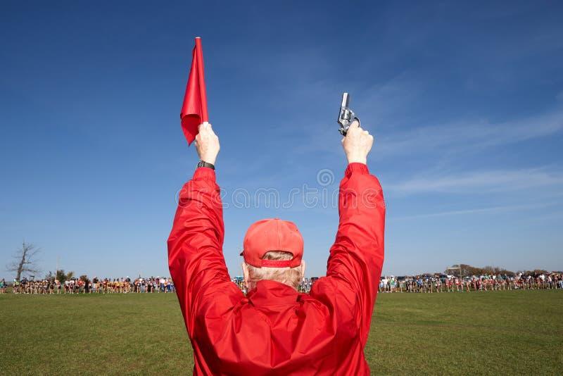 Homem que sustenta uma arma e uma bandeira do acionador de partida fotografia de stock royalty free