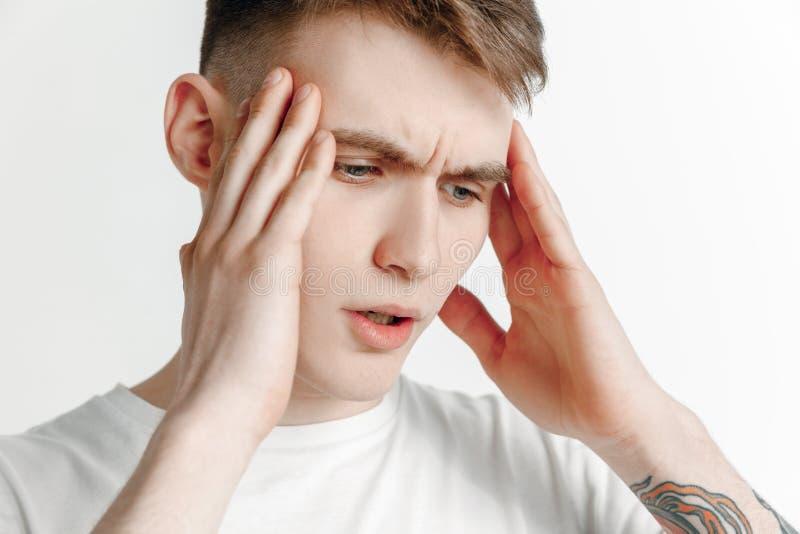 Homem que tem a dor de cabeça Isolado sobre o fundo cinzento imagens de stock