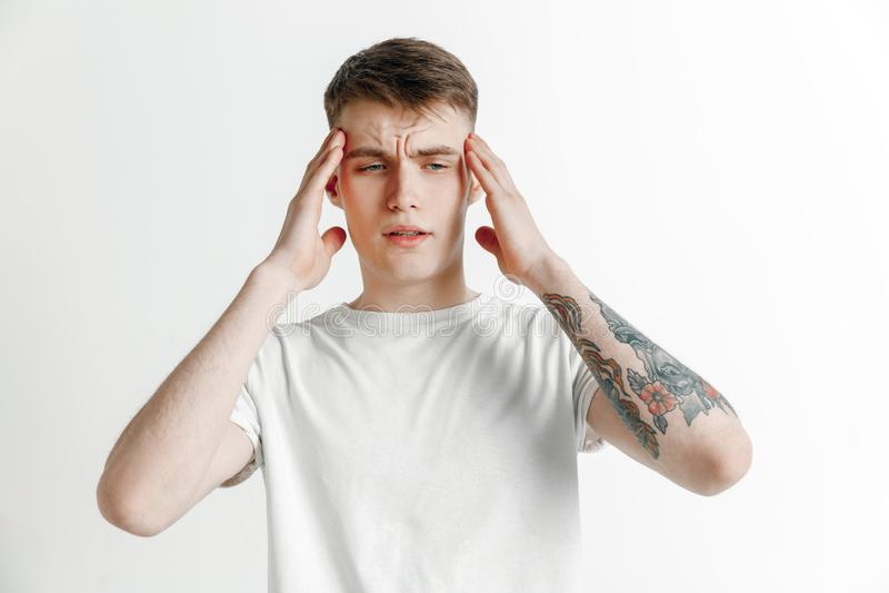 Homem que tem a dor de cabeça Isolado sobre o fundo cinzento fotos de stock royalty free