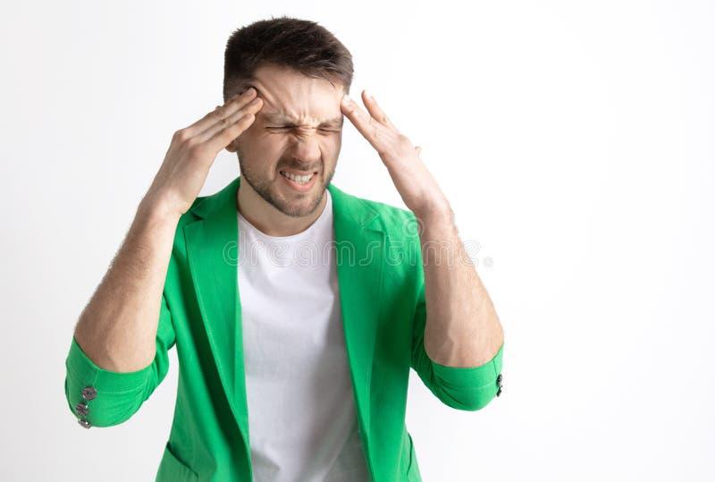 Homem que tem a dor de cabeça Isolado sobre o fundo cinzento imagem de stock royalty free