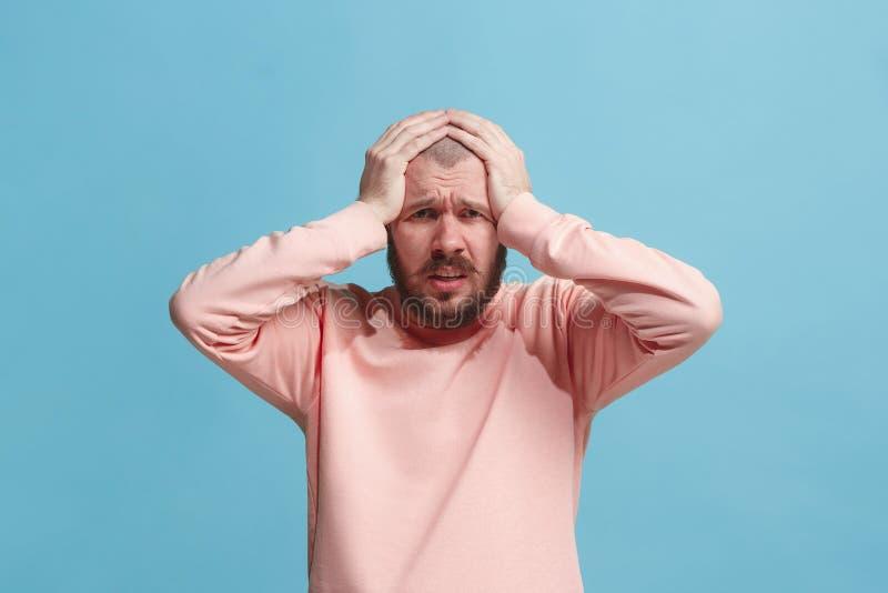 Homem que tem a dor de cabeça Sobre o fundo azul fotos de stock royalty free